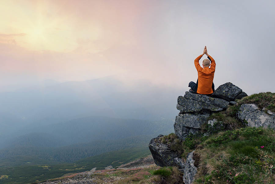 Man sitting on the cliff in yoga asana