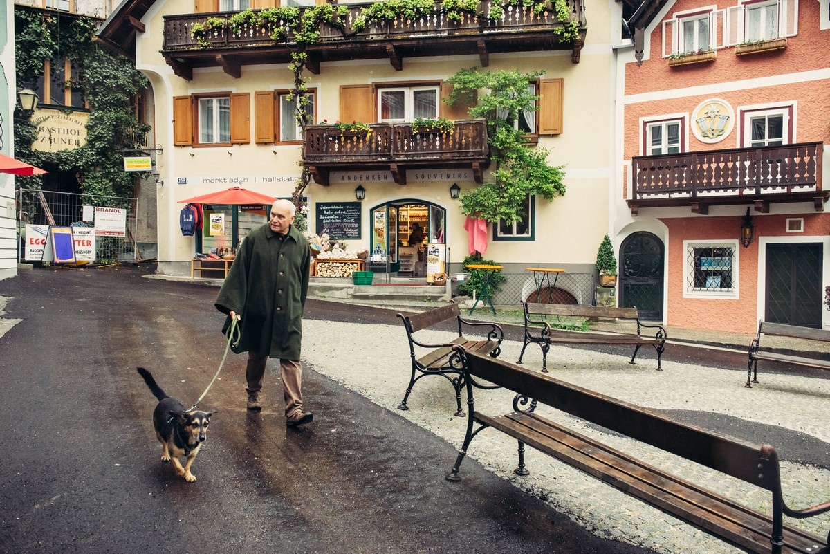 HALLSTATT, AUSTRIA - MAY 03, 2014: Local citizen on town square in Hallstatt, Austria. Hallstatt is historical village located in Austrian Alps at the Hallstatter lake and promoted by UNESCO World Heritage region.