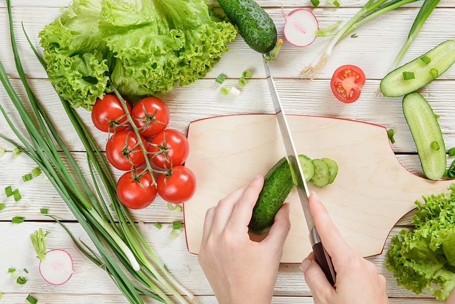 Women hands cutting cucumber and fresh ingredients (tomatoes, lettuce, onion) for the vegetable salad on white wooden background, top view
