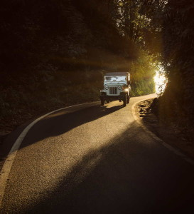 Old offroad car driving on highway inside the tunnel in the morning lighten with sunbeams in vintage tones