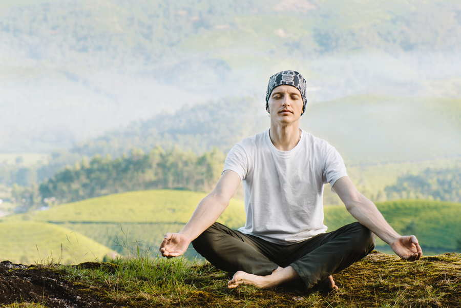 Man meditating in the nature in the morning. Doing yoga outdoors.