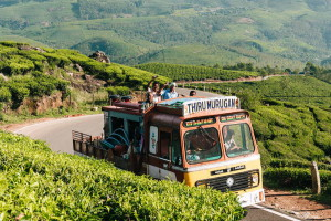 Munnar, India - December 15, 2015: Decorated truck with people in trailer going to work on tea plantations on mountain road in Munnar, India.