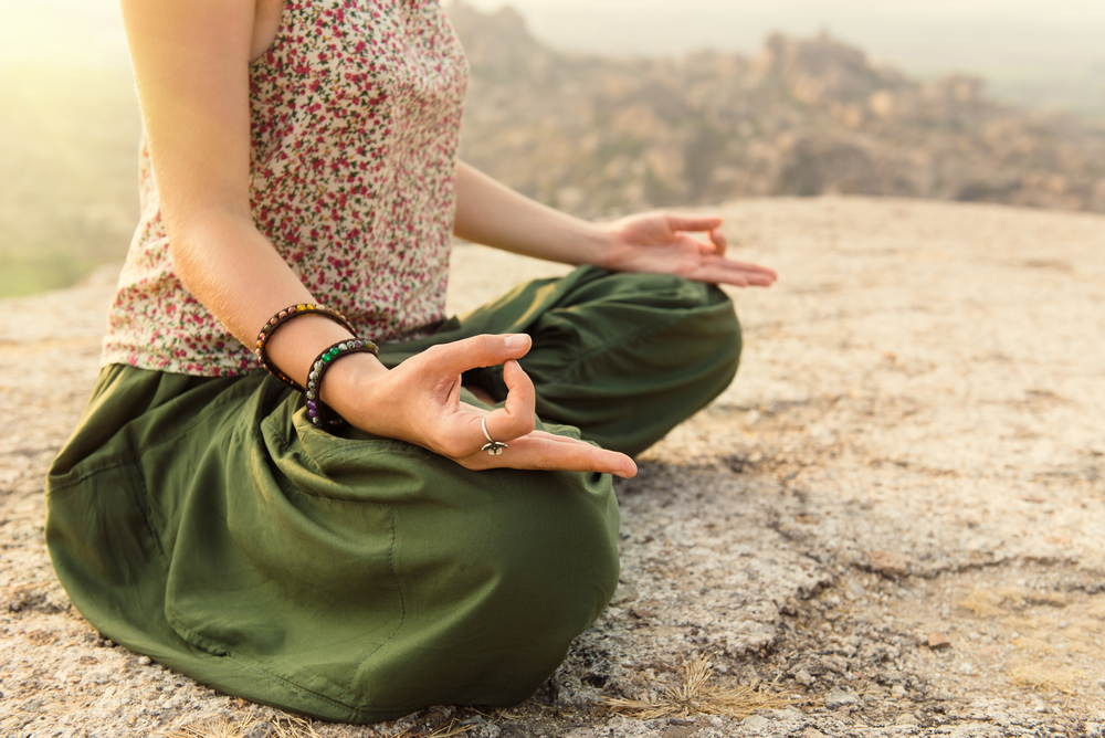 Woman meditating at rocky mountain on sunrise in Hampi, India. Close-up of hand mudra