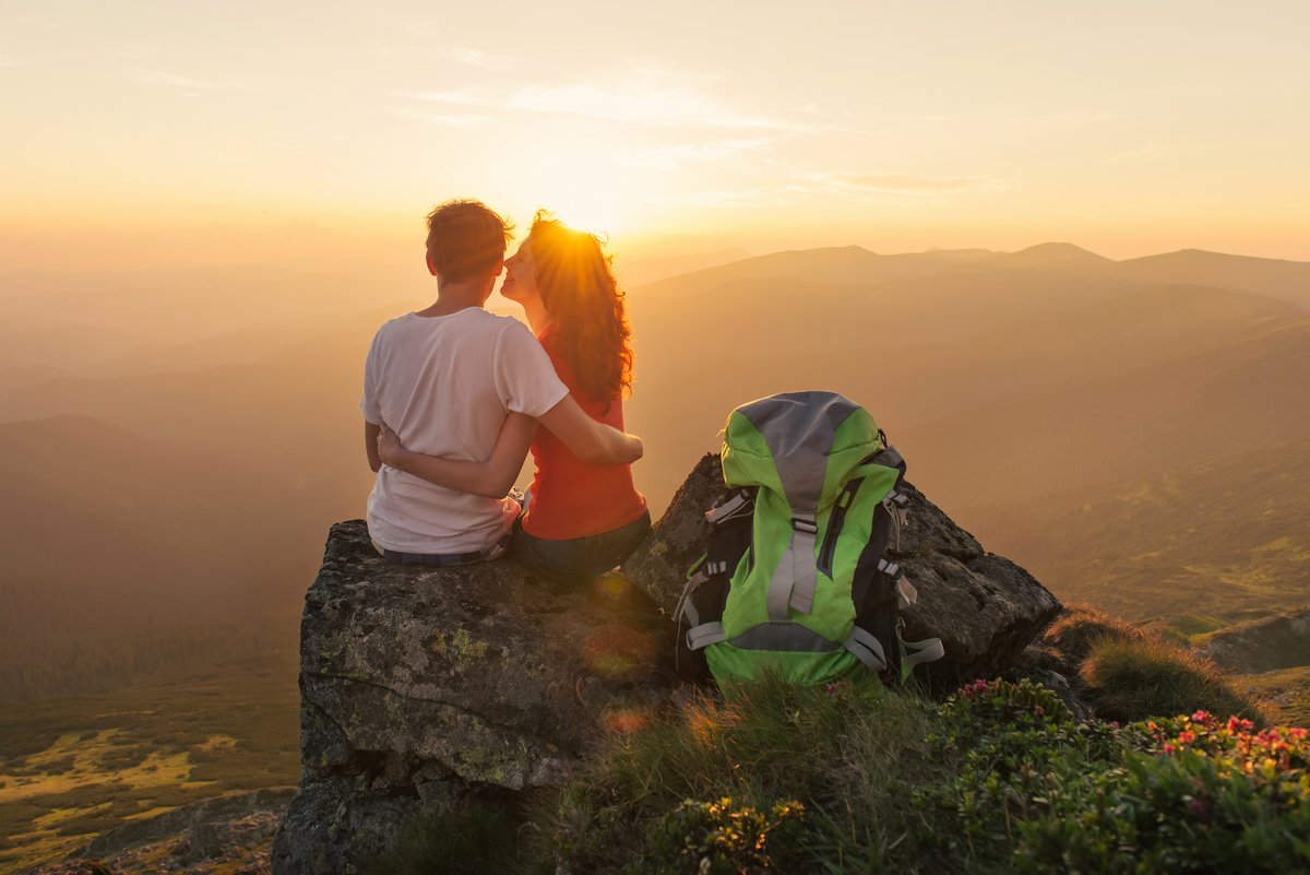 Happy couple feel freedom, kissing and enjoying the beautiful view in the mountains and looking together on sunset