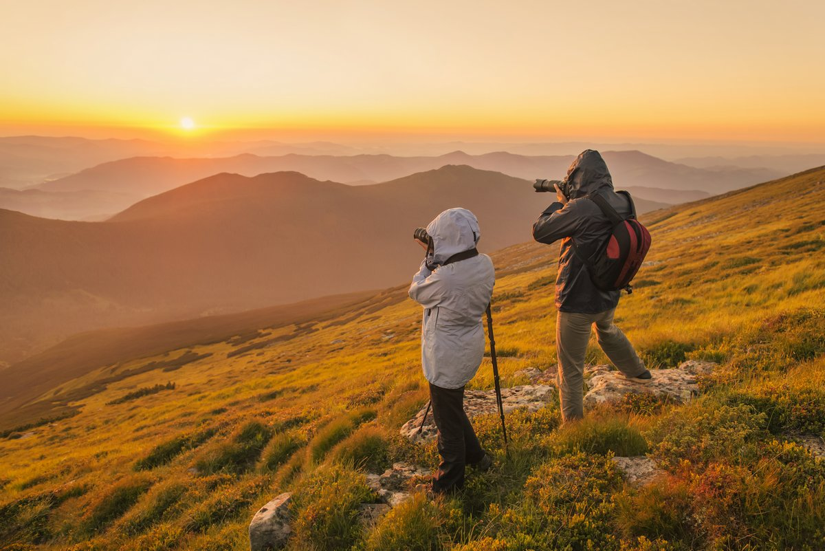 Nature photographers with digital camera and tripod on top of the mountain at sunset